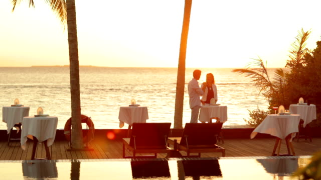 couple at tropical sunset with drinks
