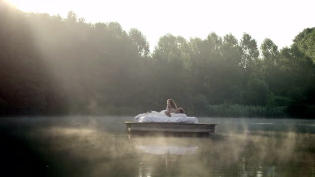 couple awakening on lake - duvet stock videos & royalty-free footage