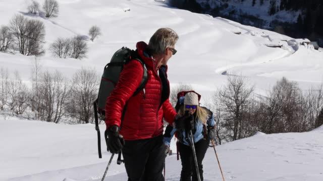 stockvideo's en b-roll-footage met couple backcountry ski above swiss village after fresh snow - ski jack