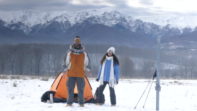 4K Couple backpackers camping in snow mountain