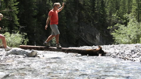 couple balance along log whie crossing creek, man offers hand - log stock videos & royalty-free footage