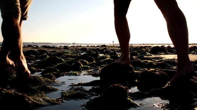 stockvideo's en b-roll-footage met couple balance on tidal rocks - de volgende stap