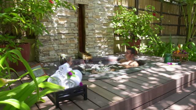 a couple bathing in a spa hot tub whirlpool bathtub hot tub. - hot tub stock videos and b-roll footage
