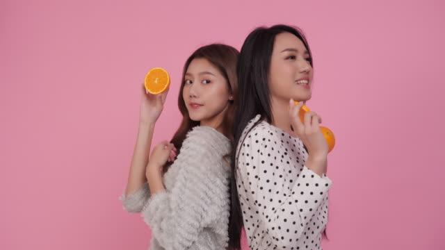 couple beauty asia teenage girl with orange fruit - ascorbic acid stock videos & royalty-free footage