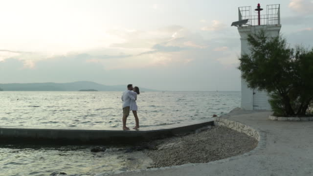 vidéos et rushes de ws couple being intimate enjoying evening walk along jetty. - embrasser sur la bouche