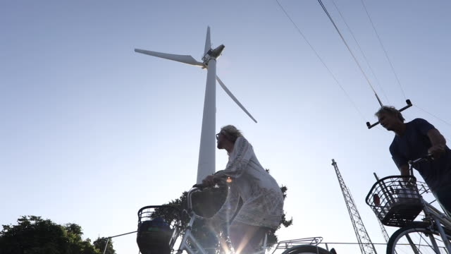 Couple bicycle past wind turbine