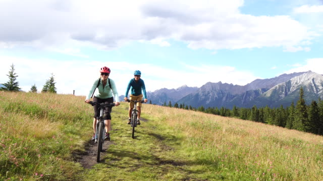 couple bike through meadow on faint track, mountains above - pedal pushers stock videos & royalty-free footage