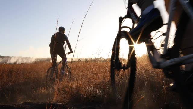 vídeos de stock, filmes e b-roll de couple bike through meadow, towards sunrise over mist - mountain bike bicicleta