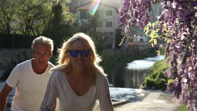 vidéos et rushes de vélo de couple sous les fleurs de la glycine, du flux ci-dessous - 55 59 ans