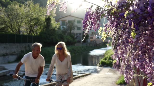couple bike under wisteria blossoms, from stream below - italy stock videos & royalty-free footage