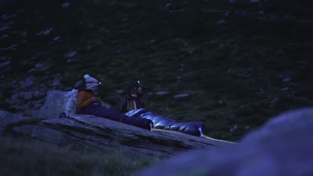 星空の下の岩の上に寝袋でカップルビビーキャンプ - 寝袋点の映像素材/bロール