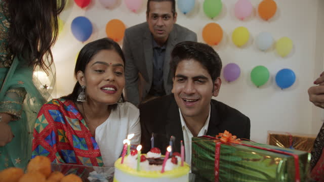couple blow candles on their cake in the presence of their friends for birthday party engagement anniversary occasion and gifts and sweets indian ladoo for celebration and decoration - life events stock videos & royalty-free footage