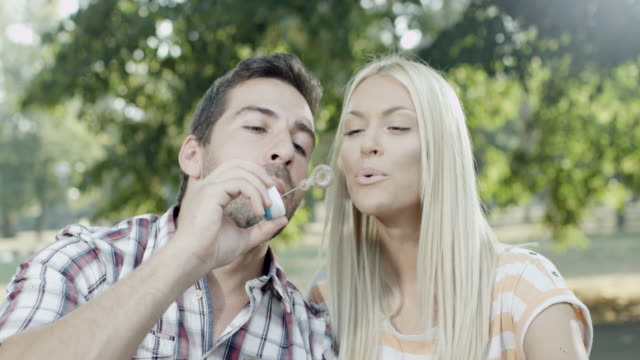 Couple blows bubbles in the park