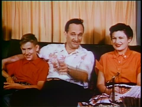 vídeos de stock e filmes b-roll de 1953 couple + boy sitting on sofa smiling + watching television / educational - prelinger archive