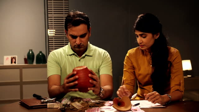 Couple breaking piggybank at home, Delhi, India