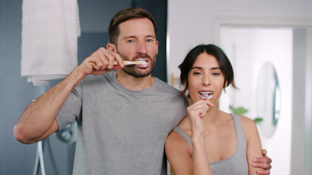 stockvideo's en b-roll-footage met couple brushing teeth - heteroseksueel koppel
