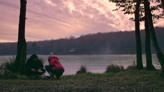 ms couple building campfire at tranquil autumn lakeside,prekmurje,slovenia - prekmurje stock videos & royalty-free footage
