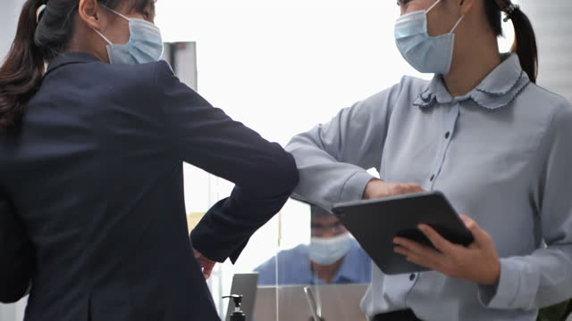 couple business woman wear surgical mask safety greeting use elbow bump - singapore stock videos & royalty-free footage