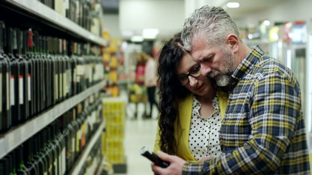 couple buying bottle of wine in supermarket - mature couple stock videos & royalty-free footage