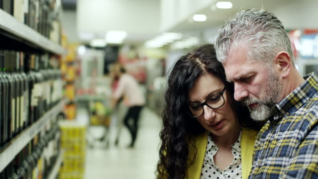 Couple buying bottle of wine in supermarket