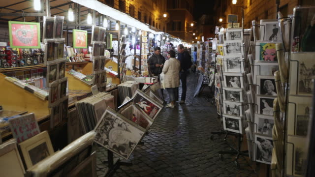 MS Couple buying card poster picture at shop with pictures on racks / Rome, Italy
