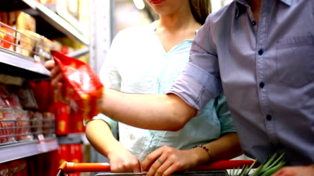 couple buying food in supermarket. - convenience food stock videos and b-roll footage