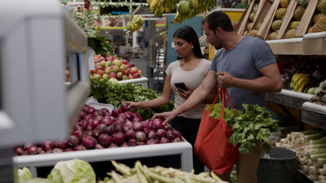 couple buying fruits and vegetables while woman looks at shopping list on smartphone's app and man holds a reusable bag - reusable bag stock videos & royalty-free footage