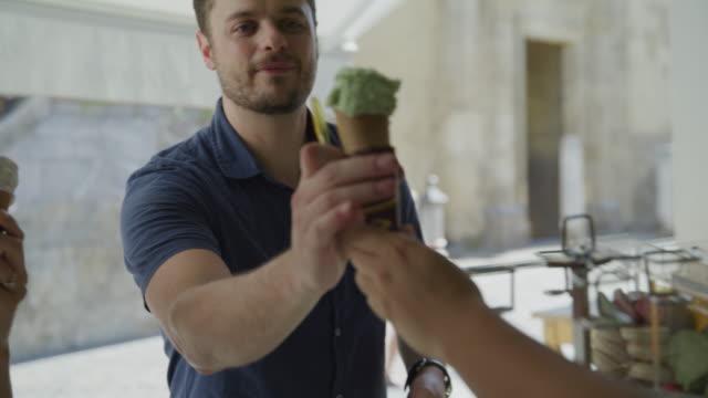 vídeos de stock e filmes b-roll de couple buying gelato cones at urban shop / cordoba, cordoba, spain - servir comida e bebida