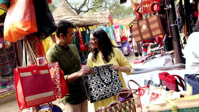 couple buying handbag at suraj kund fair, haryana, india - mercato all'aperto video stock e b–roll