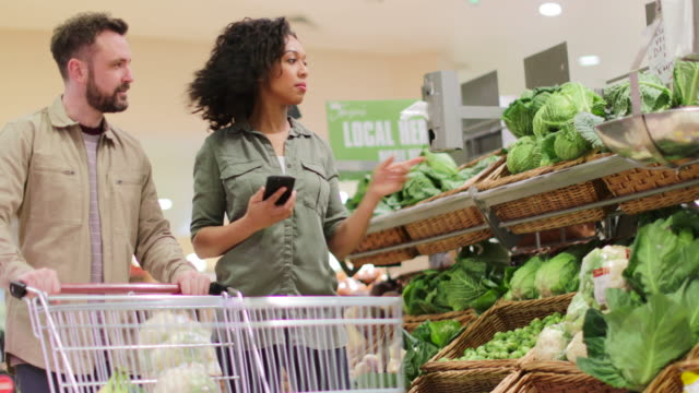 couple buying in grocery store using smartphone - wicker stock videos & royalty-free footage