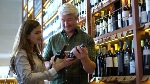 Couple buying wine at a winery and talking while choosing different wines very happy