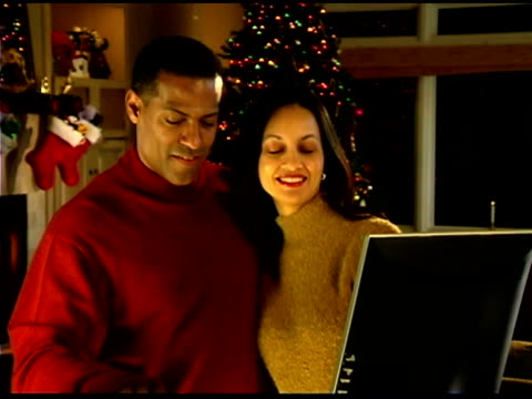 couple by christmas tree using computer - see other clips from this shoot 1407 stock videos and b-roll footage