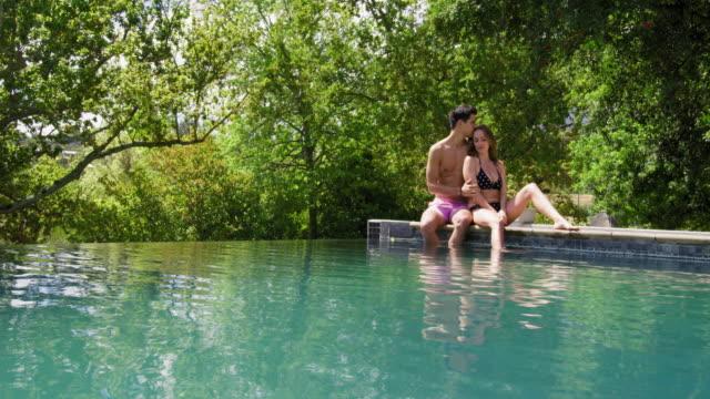 couple by pool - badbyxor bildbanksvideor och videomaterial från bakom kulisserna