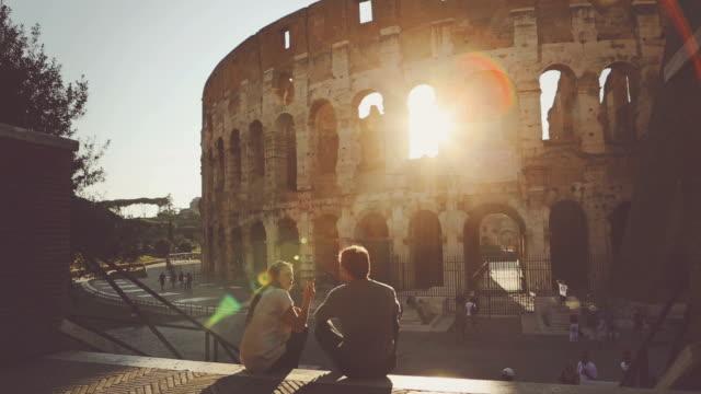 vidéos et rushes de couple au coliseum, au coucher du soleil - monument