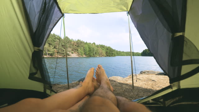 couple camping in a tent by a lake in sweden - camping stock videos & royalty-free footage