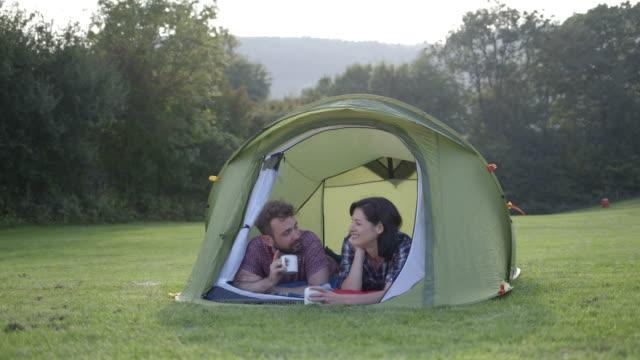 vídeos y material grabado en eventos de stock de couple camping in nature - tumbado boca abajo