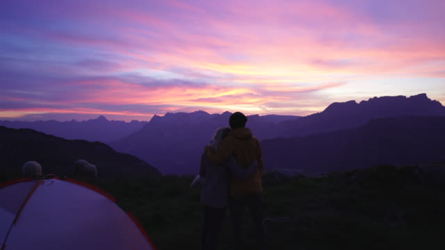 couple camping together stand in front of tent enjoy view of sunset - small group of animals stock videos & royalty-free footage