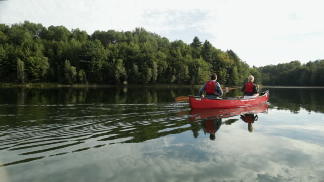 ws couple canoeing across a large lake / stowe, vermont, united states - stowe vermont stock videos & royalty-free footage