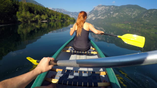 Couple canoeing on a lake towards the mountains