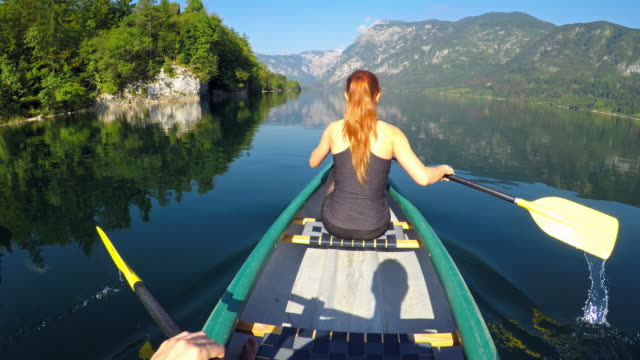 couple canoeing on a lake towards the mountains - canoeing stock videos and b-roll footage