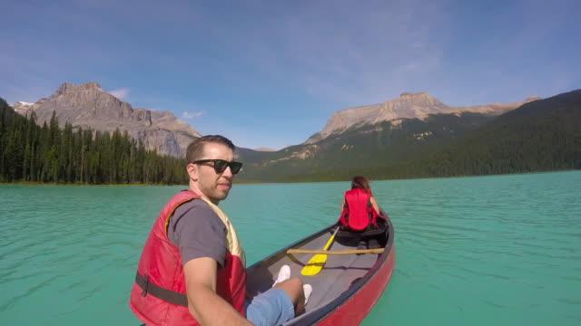 Couple canoeing on lake.