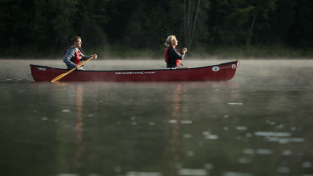ws couple canoing across a misty lake / stowe, vermont, united states - stowe vermont stock videos & royalty-free footage