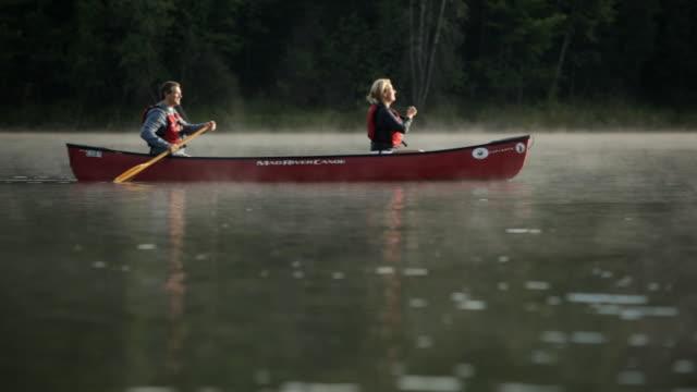 vídeos y material grabado en eventos de stock de  ws couple canoing across a misty lake / stowe, vermont, united states - pareja de mediana edad