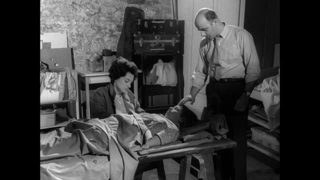 1968 a couple care for unconscious child - fieber stock-videos und b-roll-filmmaterial