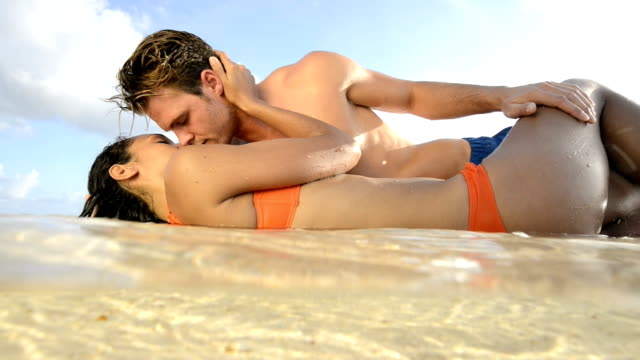 Couple caressing and kissing in the sea