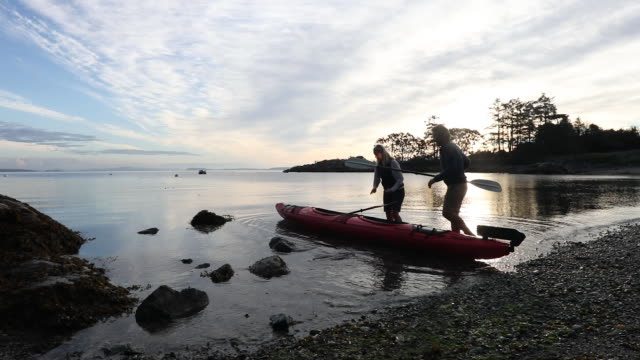 couple carry 2 person kayak into tidal lagoon, sunrise - kayaking stock videos & royalty-free footage