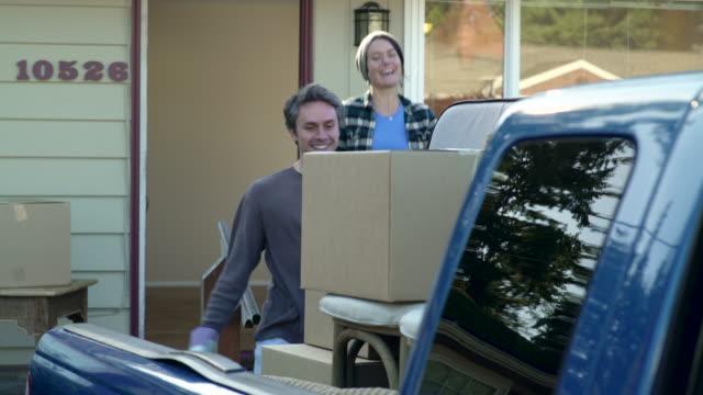 vidéos et rushes de couple carrying boxes into new home from van. - couple d'âge moyen