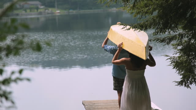 couple carrying canoe on wooden dock over lake - carrying stock-videos und b-roll-filmmaterial