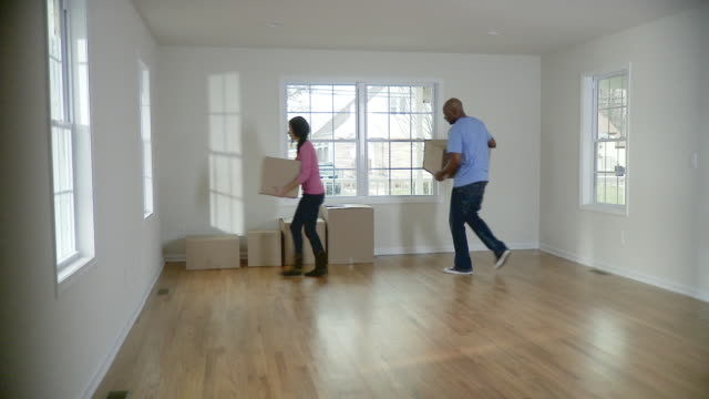 WS, Couple carrying cardboard boxes in empty room, Plainfield, New Jersey, USA