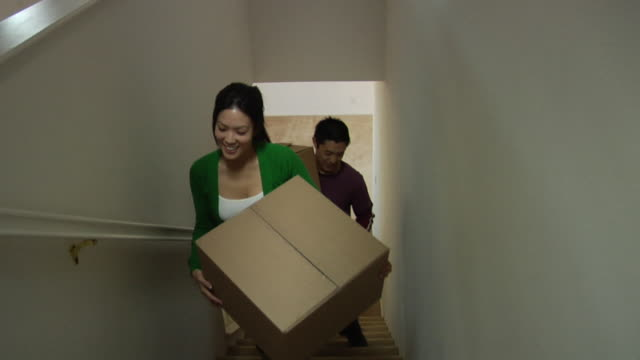 WS Couple carrying cardboard boxes up stairs in new house / Los Angeles, California, USA